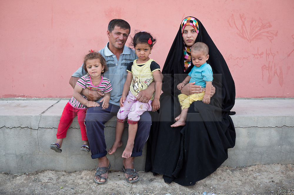 © Licensed to London News Pictures. 25/06/2014. Khanaqin, Iraq. 37 year old Salh Madi (2L) is pictured with his family, Malak (3), Aya (5), his wife Rafida Ha'di (23) and their one year old son Bilal, all Iraqi refugees from the front line town of Jalawla, at the Bahari Taza refugee camp in Iraq. Salh and Rafida escaped the town with their Tukman family after fighting commenced between ISIS and Kurdish Peshmerga forces. Located on the outskirts of Khanaqin, a town just 20 minutes from the front-line of the battle with ISIS insurgents, the Bahari Taza refugee camp, and its satellite camps, now house around 600 families from southern Iraq. Built by the local village leader to meet the influx of refugees from nearby Jalawla and Saidia, where intense fighting is still taking place. Turkman, Arab and Kurd, both Sunni and Shia, all live together in tents, barns and unfinished buildings waiting for the conflict to end. Photo credit: Matt Cetti-Roberts/LNP