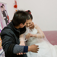 A bride fends off attacks by drunken male wedding guests in Suining, Jiangsu Province, China. These assaults vary from playful to aggressive and are a traditional way that the bride displays her fidelity to her new husband.