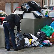 Nederland Rotterdam 4 november 2008 20081104 Foto: David Rozing..Man zet vuilniszak naast overvolle ondergrondse afvalcontainer in achterstandswijk Delfshaven. Veel afvalzakken staan naast de containers omdat deze er niet meer bij passen.  Op de afvalcontainers staat aangegeven dat foutief aanbieden van afval beboet kan worden. ..Foto David Rozing