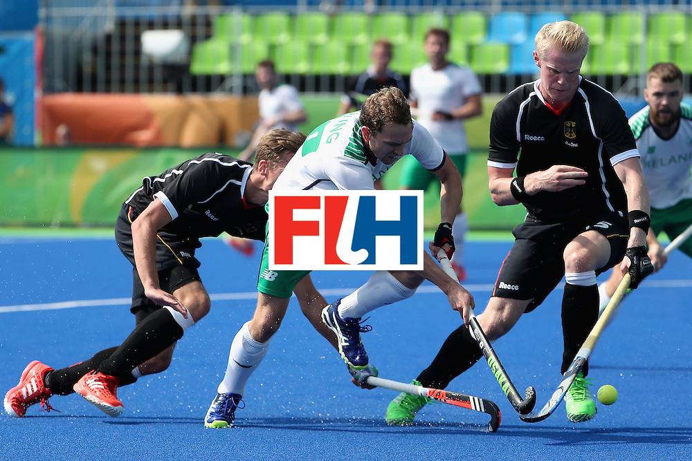 RIO DE JANEIRO, BRAZIL - AUGUST 09:  Michael Darling #20 of Ireland moves the ball past Mathias Muller #2 and Tom Grambusch #15 of Germany during the hockey game on Day 4 of the Rio 2016 Olympic Games at the Olympic Hockey Centre on August 9, 2016 in Rio de Janeiro, Brazil.  (Photo by Christian Petersen/Getty Images)
