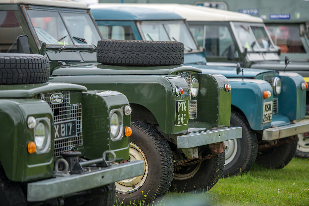 Collection of vintage land rovers lined up in a neat row, Masham, North Yorkshire, UK