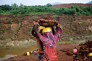 Workers carry chromite-ore to trucks at the Kamardha chromite mine. Sukinda, Orissa, India
