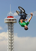 Joey Cordova, 21, of Longmont, Co.gets inverted with the tower at Elitch Gardens in the background during the BMX Dirt Open Qualifier at the Dew Action Sports Tour, the only season-long professional action sports tour. The event will make its second stop of the season in Denver with the Right Guard Open taking place Thursday July 13 through Sunday July 16, 2006 in and around the Pepsi Center. Athletes were already in town for practice sessions and qualifying rounds on Wednesday July 12, 2006..(MARC PISCOTTY/ © 2006)