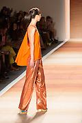 Glittery orange pants and an orange tunic sleveless top.