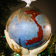 "An art sculpture of a globe with hands and a dove on the shore of Hoan Kiem Lake in Hanoi, Vietnam. The sculpture is titled ""Hope & Love for Peace."" Night shot."