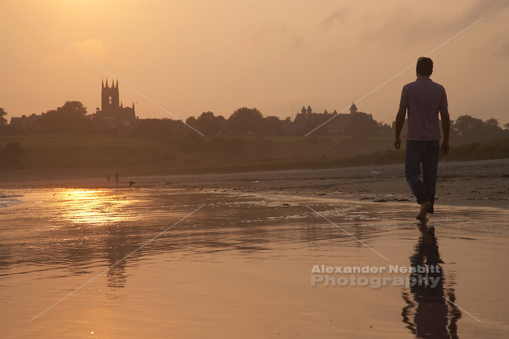 Newport, RI 2006 - A Man walks alone down deserted Sachuest Beach (second) toward the St George's church in the distance.  The wet sand show his reflection and the glare of the sunset.