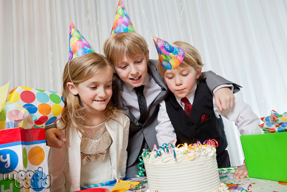Brothers and sister wearing party hat looking at birthday cake together