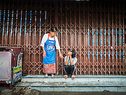 10 SEPTEMBER 2015 - BANGKOK, THAILAND:  Women stand in front of Chaiyasit Kittiwanitchapant's home at Wat Kalayanamit. Authorities started to destroy 54 homes in front of Wat Kalayanamit, a historic Buddhist temple on the Chao Phraya River in the Thonburi section of Bangkok. Government officials, protected by police, seized the house of Chaiyasit Kittiwanitchapant, a Kanlayanamit community leader, who has led protests against the temple's abbot for trying to evict community members whose houses are located around the temple. Work crews went into Chaiyasit's home and took it apart piece by piece. The abbot of the temple said he was evicting the residents, who have lived on the temple grounds for generations, because their homes are unsafe and because he wants to improve the temple grounds. The evictions are a part of a Bangkok trend, especially along the Chao Phraya River and BTS light rail lines, of low income people being evicted from their long time homes to make way for urban renewal.    PHOTO BY JACK KURTZ