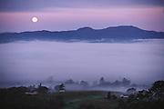 Foggy moonrise looking west over the western hills of Napa Valley from Menzel house, California.