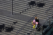 A single mother struggles down Westfield shopping mall steps laden with children's pink bike and birthday balloons.