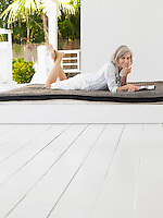 Woman lying down on daybed on verandah portrait