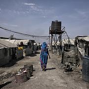 Une femme de l'ethnie shilluk marche dans une ruelle du camp de protection des civils de la Mission des Nations Unies au Soudan du Sud, la Minuss, de Malakal.