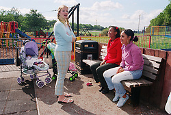 Young mothers talking together in children's playground with children in pushchairs,