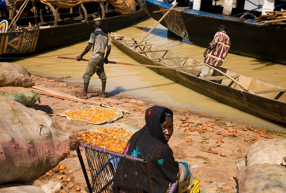 """A woman waits by the river selling dried fruit while men manouver a """"pinasse"""", the tipical canoe from this regions. At the confluence of the Niger and the Bani rivers, between Timbuktu and Segou, Mopti is the second largest city in Mali, and the hub for commerce and tourism in this west-african landlocked country."""
