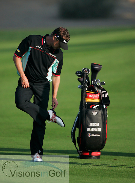 Joakim Haeggman cleans his shoes and spikes on the 1st day of the Dubai Desert Classic, UAE 030305
