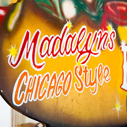 """Sign for Madalyn the Hot Dog Lady of Crown Point Indiana in 2010. Sadly, Madalyn hasn't been in the square for the summer of 2011 and has apprantly retired. She was a part of life in Crown Point for a long time and will be missed. Crown Point is located in Northwest Indiana with a population of over 37,000. Crown Point and Lake County are about 50 miles from Chicago and are considered part of the """"Chicagoland"""" area. Crown Point has a traditional small town America feel with a main street consisting of the old Lake County Courthouse surrounded by numerous small businesses, known as """"the square"""", including a theater, ice cream shop, antique stores, and restaurants."""