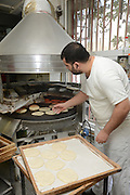 Pita Bakery. The baker removes the pita from the oven