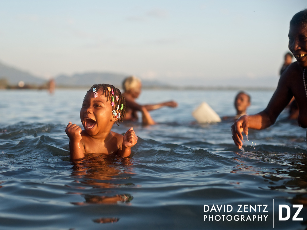 A child laughs with delight while playing with her mother and grandmother during a sunrise voodou ritual at Bord de Mer de Limonade, on the north coast of Haiti on July 25, 2008. After renewing their faith in the mud pit at Plaine du Nord on the days prior, pilgrims migrate to the nearby water, their faith renewed.