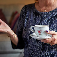 A photograph of a woman having a cup of tea in a Middlesborough football club cup while talking animatedly in North East England