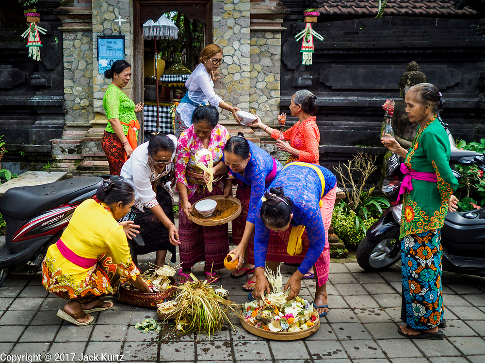 "08 AUGUST 2017 - UBUD, BALI, INDONESIA: Women leave offerings at an entrance to their family compound during a ceremony to honor a family temple in Ubud, Bali. Balinese Hindus have a 210 day calender and every almost every family compound on Bali has a family temple. Once a year (or every 210 days) families celebrate the ""birthday"" of their temple with a ceremony.     PHOTO BY JACK KURTZ"