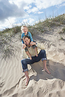 Girl (5-6) sitting on father's shoulders on beach portrait