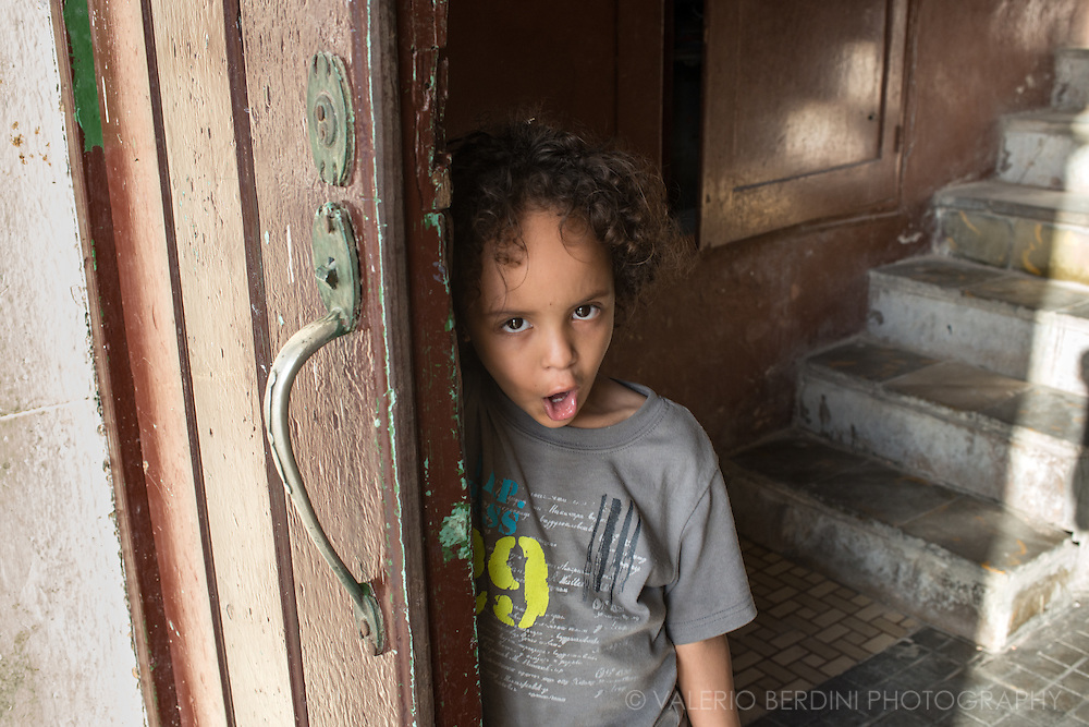 A young boy pulls a face on the entrance door of a building in Plaza Vieja in Old Havana, Cuba.