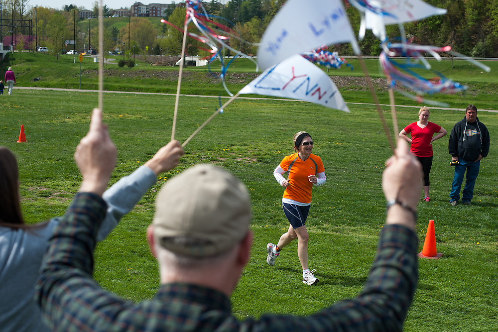 Lynn Hanna races to the finish of the Race for a Reason 5k as her friends cheer her on. Photo by: Ross Brinkerhoff. Race for a Reason, Race 4 A Reason, Annual Events, Events, Students, Faculty & Staff