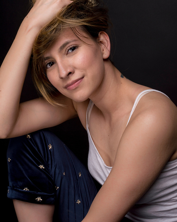 Female model in studio, dark background, soft light wearing tank top with blue pants