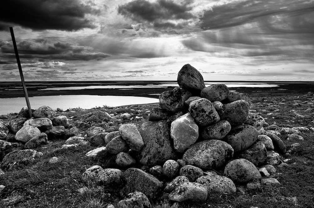 CANADA, Nunavut.Landscape with ancient burial site on a stormy day