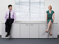 Businesspeople sitting on office cabinets