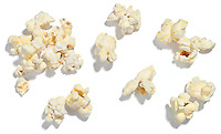 Popped popcorn kernels on white background.