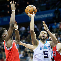 03 November 2015: Charlotte Hornets forward Nicolas Batum (5) takes a jump shot past Chicago Bulls forward Nikola Mirotic (44) and Chicago Bulls guard Jimmy Butler (21) during the Charlotte Hornets  130-105 victory over the Chicago Bulls, at the Time Warner Cable Arena, in Charlotte, North Carolina, USA.