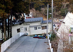 London News Pictures. 20/03/2011. Onagawa, Japan, the road to the sea is blocked by this house which was picked up and deposited on the road by the wave.Thousands are missing after a 9.0 magnitude strong earthquake struck on March 11 off the coast of Japan causing a tsunami wave. Photo credit should read Alex Tee/London News Pictures.