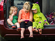 26 JUNE 2019 - CENTRAL CITY, IOWA: PAIGE MILLER, 3, AVERY MILLER, 9, and ANNALIESE MILLER, 4, in dinosaur outfit, watch a video on a smart phone at the Linn County Fair. Summer is county fair season in Iowa. Most of Iowa's 99 counties host their county fairs before the Iowa State Fair, August 8-18 this year. The Linn County Fair runs June 26 - 30. The first county fair in Linn County was in 1855. The fair provides opportunities for 4-H members, FFA members and the youth of Linn County to showcase their accomplishments and talents and provide activities, entertainment and learning opportunities to the diverse citizens of Linn County and guests.       <br /> PHOTO BY JACK KURTZ