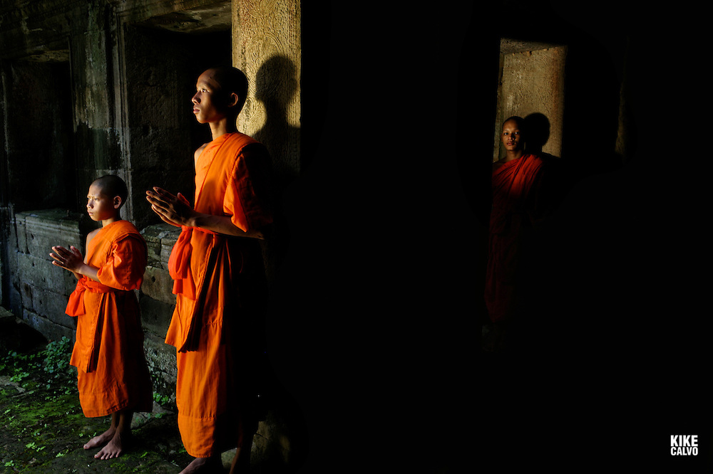 Theraveda Buddhist monks at the ancient ruins of Bayon Temple, Angkor, Cambodia.