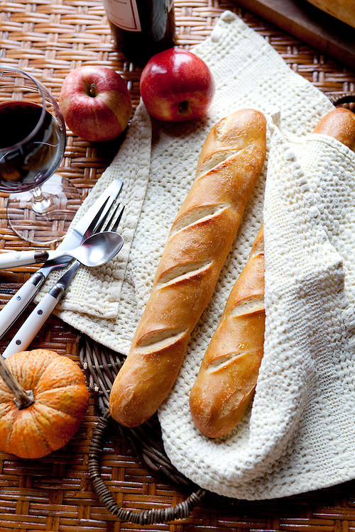 A fall picnice of wine, apples and fresh baked french baguettes.