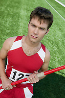 Male athlete holding javelin, portrait
