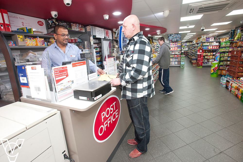 Pictured is postmaster Anand Soori serving Peter Jablonski<br /> <br /> Waller Avenue Post Office, Luton<br /> <br /> March 27, 2015