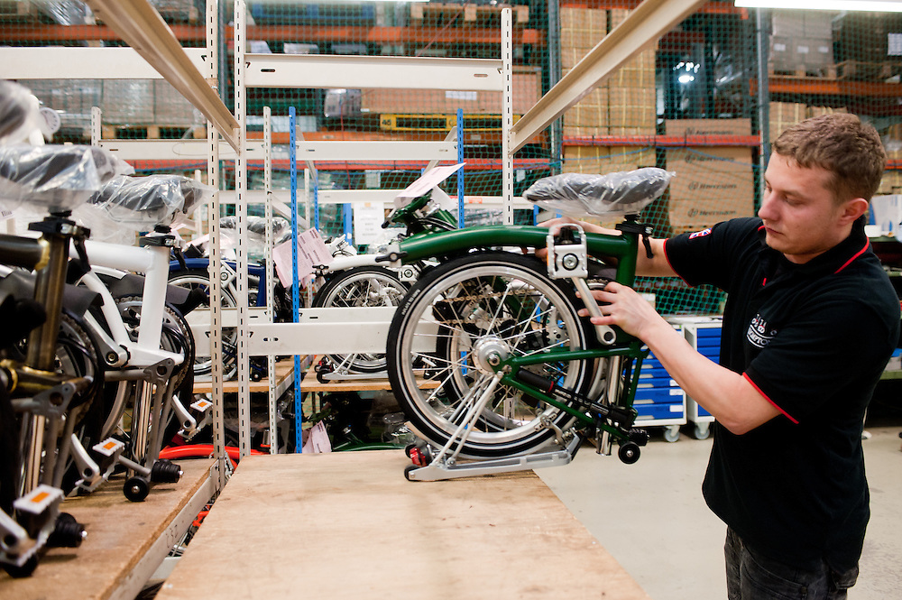 London, UK - 29 January 2013: a workman stocks a collapsed folding bike in the Brompton Bicycle factory in South West London. The company was founded in 1976 by Andrew Ritchie and is one of only two major frame manufacturers still based in the UK. Today, Bromptons are sold in 42 export markets.