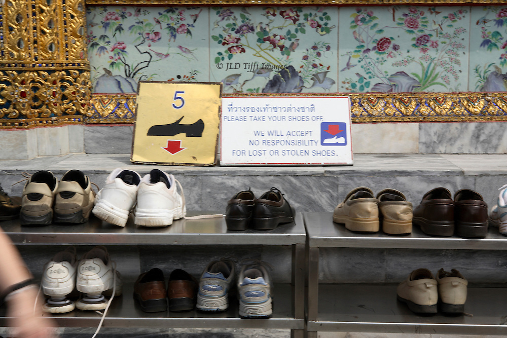 Shelf of shoes outside a Thai religious shrine.  Visitors are politely asked to remove them.