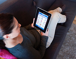 Woman using iPad computer tablet at home to look at Facebook internet website