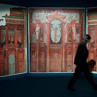 "MILAN, ITALY - JUNE 01:  A Palazzo Reale employee walks in front of a murals of ""Second Pompeian Style"", dating from 100 years BC, at ""I due Imperi"" exhibition on June 1, 2010 in Milan, Italy. The Exhibition illustrates the birth and development of the Roman Empire and the Empire of the Chinese Qin and Han Dinasties  (Photo by Marco Secchi/Getty Images)"