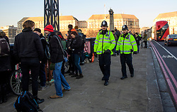 © Licensed to London News Pictures. 20/01/2017. London, UK.  Police watch over the demo. As part of the 'Bridges not Walls' campaign of national demonstrations against Donald Trump, a banner is suspended from Lambeth Bridge in London showing the Houses of Parliamnet. Donald Trump will attend his inauguration ceremony in Washington later today. Photo credit: Ben Cawthra/LNP