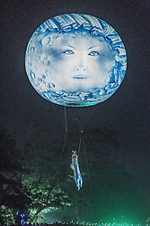 © Licensed to London News Pictures . 19/07/2013 . Suffolk , UK . Hundreds watch as a woman suspended from a moon balloon as Studio Festi perform Water Dance above a lake in Henham Park after sunset on the opening night of The Latitude music and culture festival in Henham Park , Southwold . Photo credit : Joel Goodman/LNP
