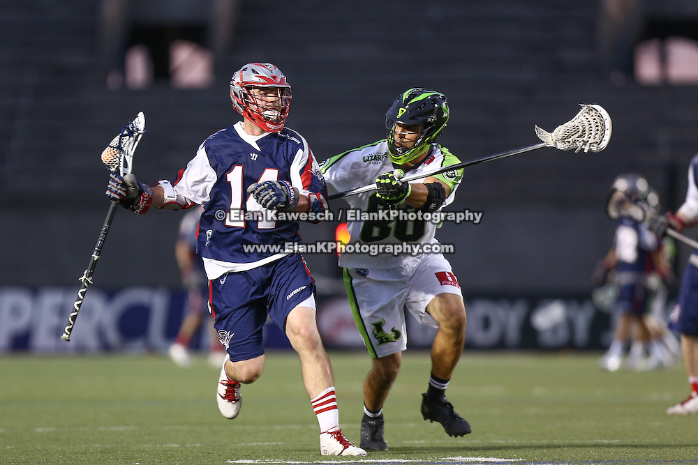 Ryan Boyle #14 of the Boston Cannons keeps the ball away from Steve Holmes #80 of the New York Lizards during the game at Harvard Stadium on July 19, 2014 in Boston, Massachusetts. (Photo by Elan Kawesch)