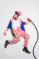 Uncle Sam lying dead on the ground with gasoline nozzle and hose still in his hand..Model Release: 20080626_MR_A