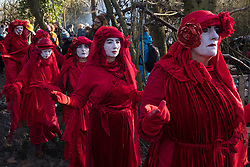 Harefield, UK. 18 January, 2020. The Red Rebel Brigade shows support for activists from Extinction Rebellion, Stop HS2 and Save the Colne Valley who reoccupied the Colne Valley wildlife protection camp on the second day of a three-day 'Stand for the Trees' protest in the Colne Valley timed to coincide with tree felling work by HS2. Bailiffs acting for HS2 had evicted all but two activists from the camp the previous week. 108 ancient woodlands are set to be destroyed by the high-speed rail link.