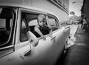 A young boy waits in the front seat for his father to return.