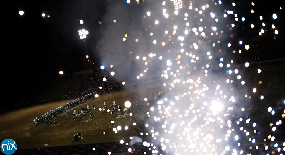 Kannapolis and Hickory Ridge players meet a center field at the conclusion of their game as fireworks go off on Plummer's Perch Friday next to Kannapolis Memorial Stadium. The Wonders won the game 47-0. (Photo by James Nix)
