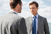 Businessmen looking at each other against sky